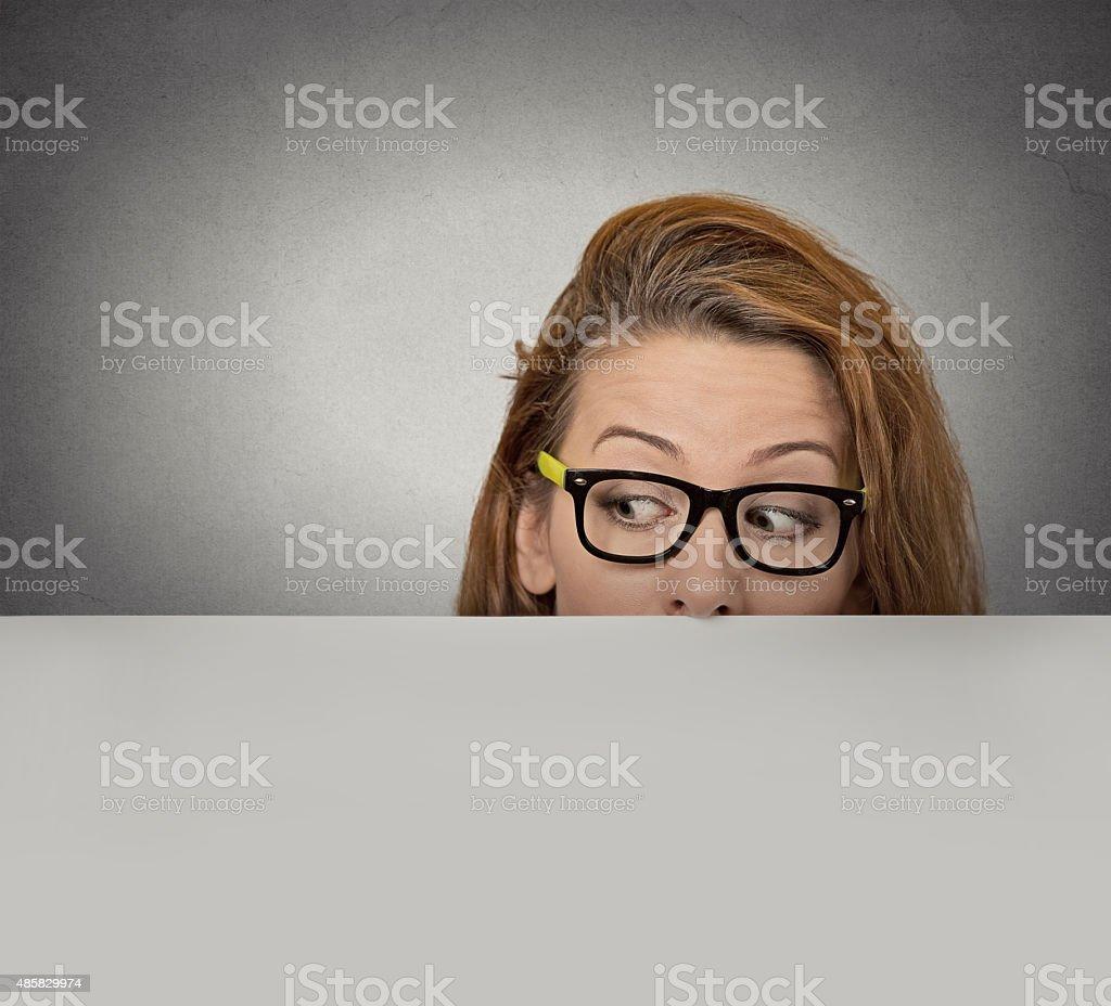 Curious woman peeking over edge of blank paper billboard stock photo