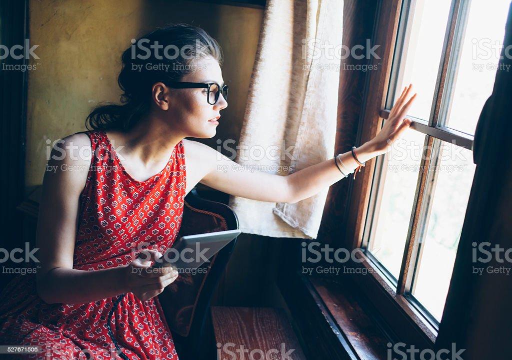 Curious young woman peek through the window stock photo