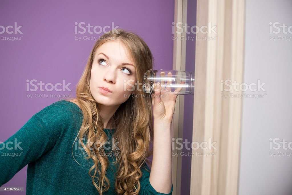 Curious young woman with glass stock photo