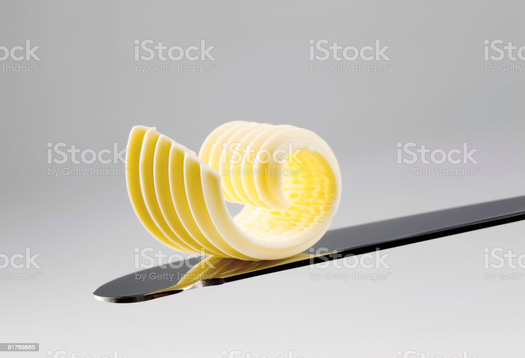Curl of butter on the end of knife royalty-free stock photo