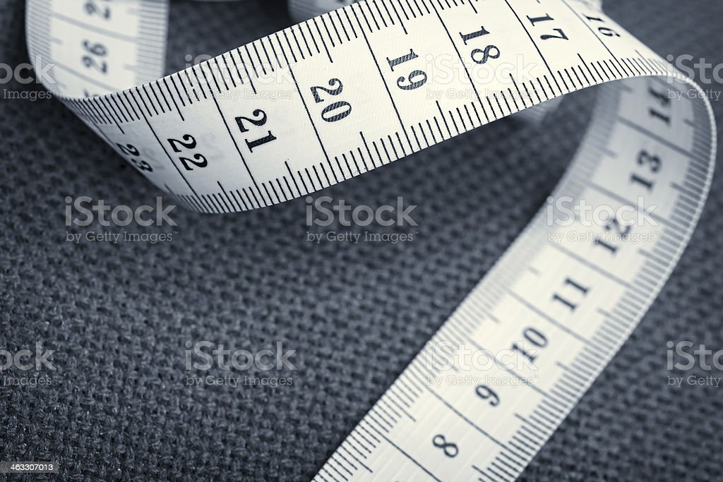 Curled measuring tape on a gray canvas stock photo