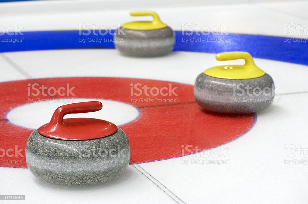 Curling equipment laying on a bullseye stock photo