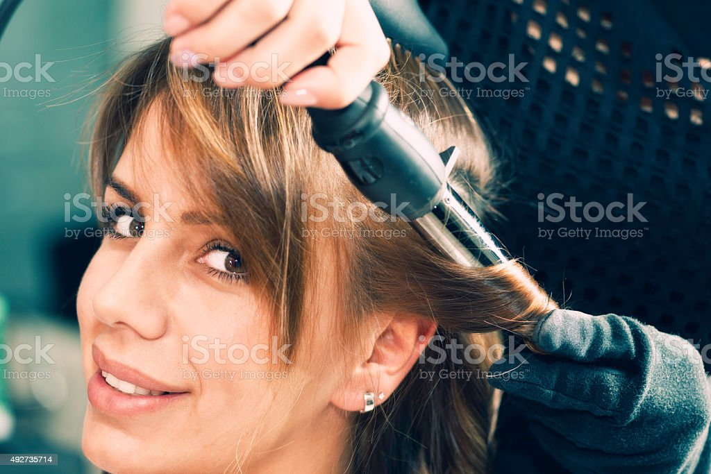 Curling hair with curling iron stock photo