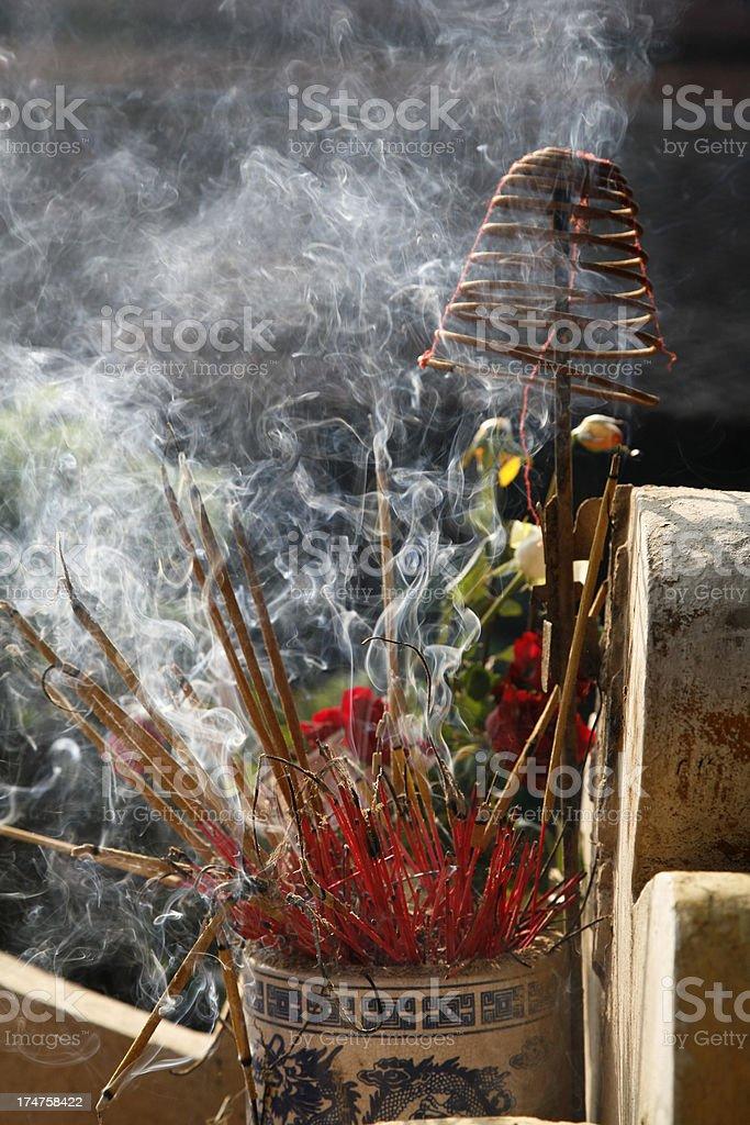 Curling smoke from burning incense sticks stock photo