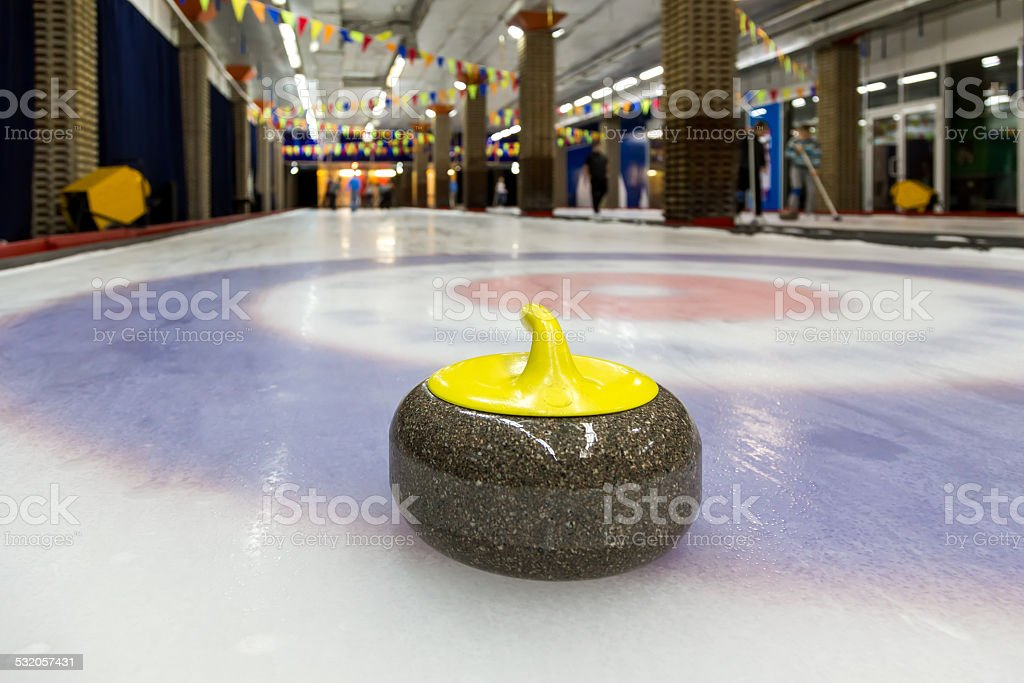 Curling stones on an indoor rink stock photo