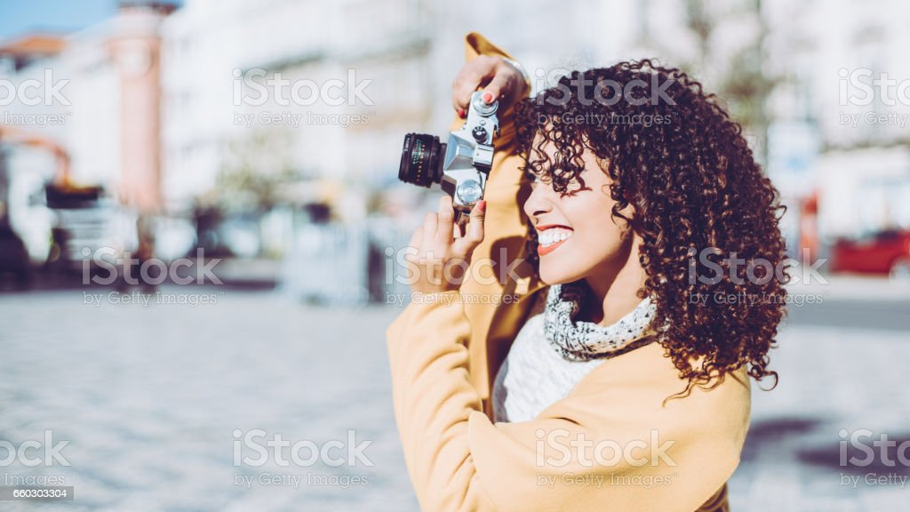 Curly beautiful woman with retro photo camera stock photo