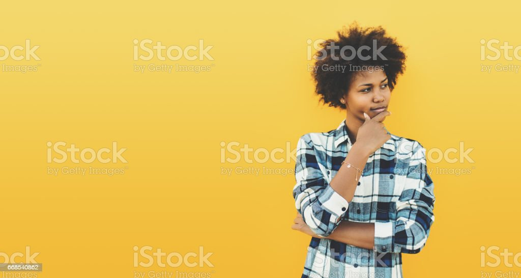 Curly black feemale on yellow background stock photo