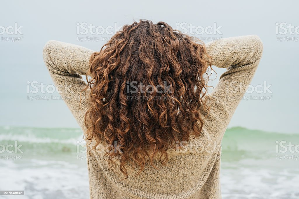 Curly brunette in a sweater on the coast stock photo
