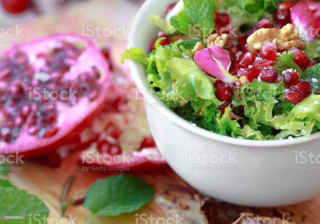 Salada de endívia crespa com romã, nozes, pétalas de rosa. foto royalty-free