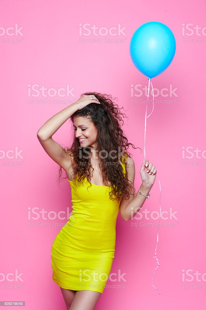 Curly girl in a yellow dress on a pink background stock photo