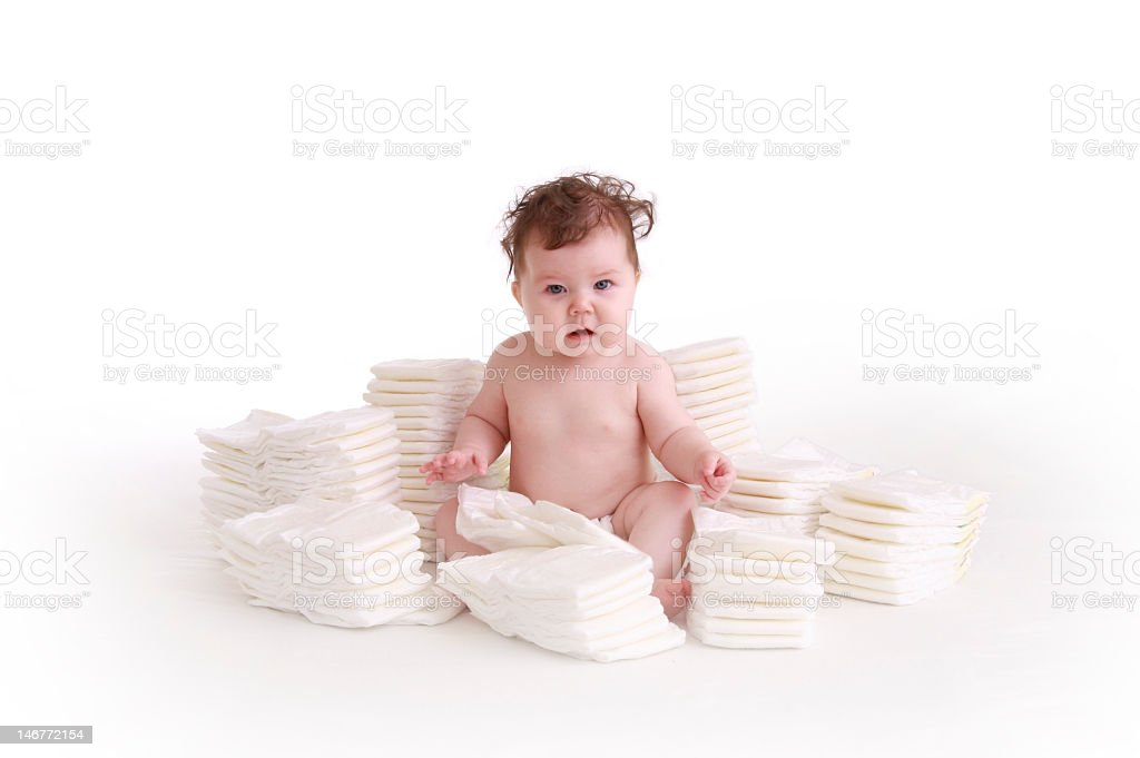 Curly haired baby sitting in a pile of diapers stock photo