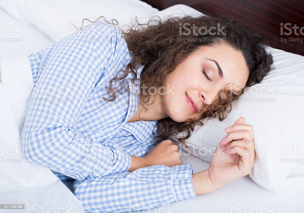 Curly haired girl having a nap in bed stock photo