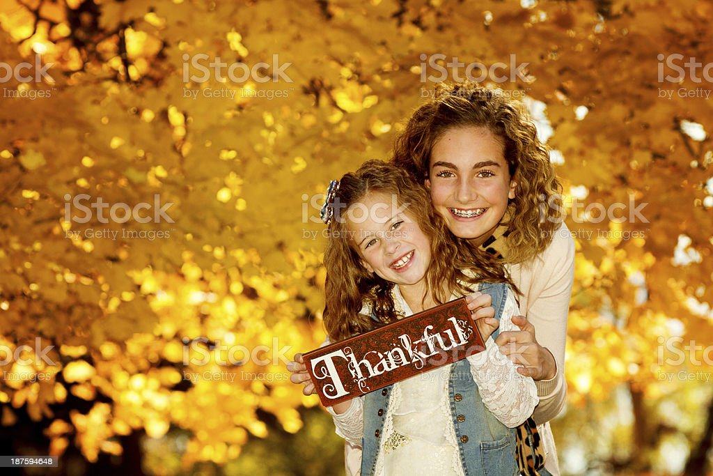 Curly haired sisters hold thankful sign in front of trees royalty-free stock photo