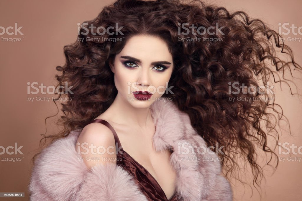 Curly hairstyle. Fashionable elegant woman with makeup and blowing healthy long hair posing in pink fur coat isolated on beige background. Winter fashion closeup portrait. stock photo