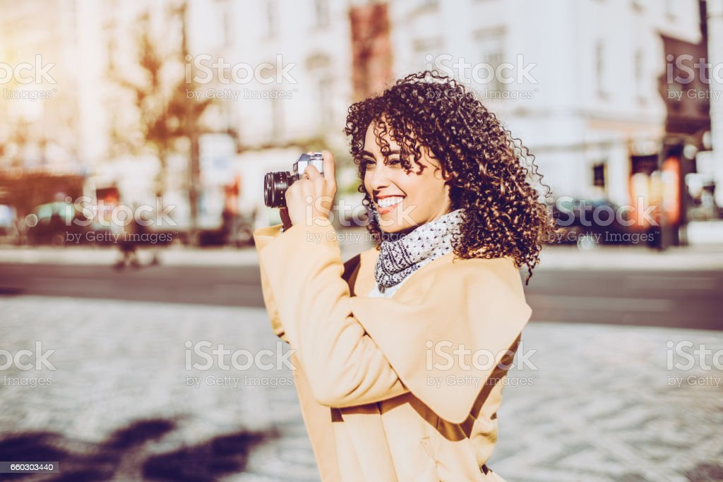 Curly laughing girl with vintage photo camera stock photo