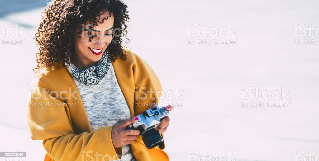 Curly smiling woman with vintage camera stock photo