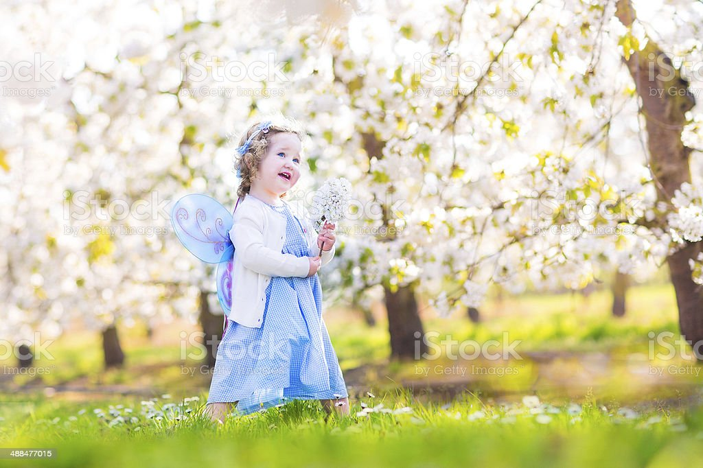 Curly toddler girl in fairy costume playing into fruit garden stock photo