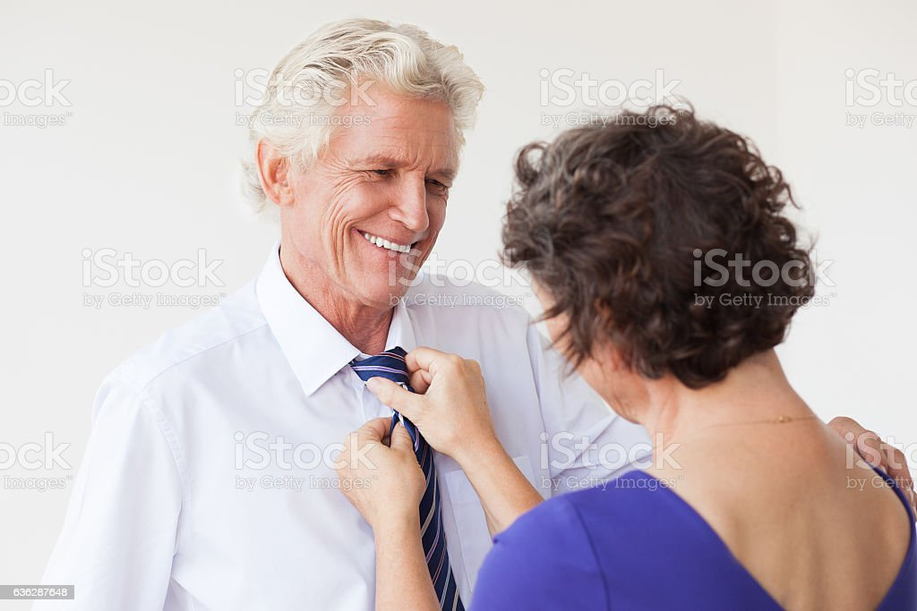 Curly wife helping husband to tie necktie stock photo