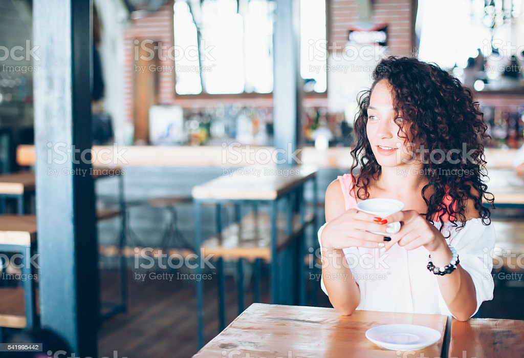 Curly young woman drinking coffee in a bar stock photo