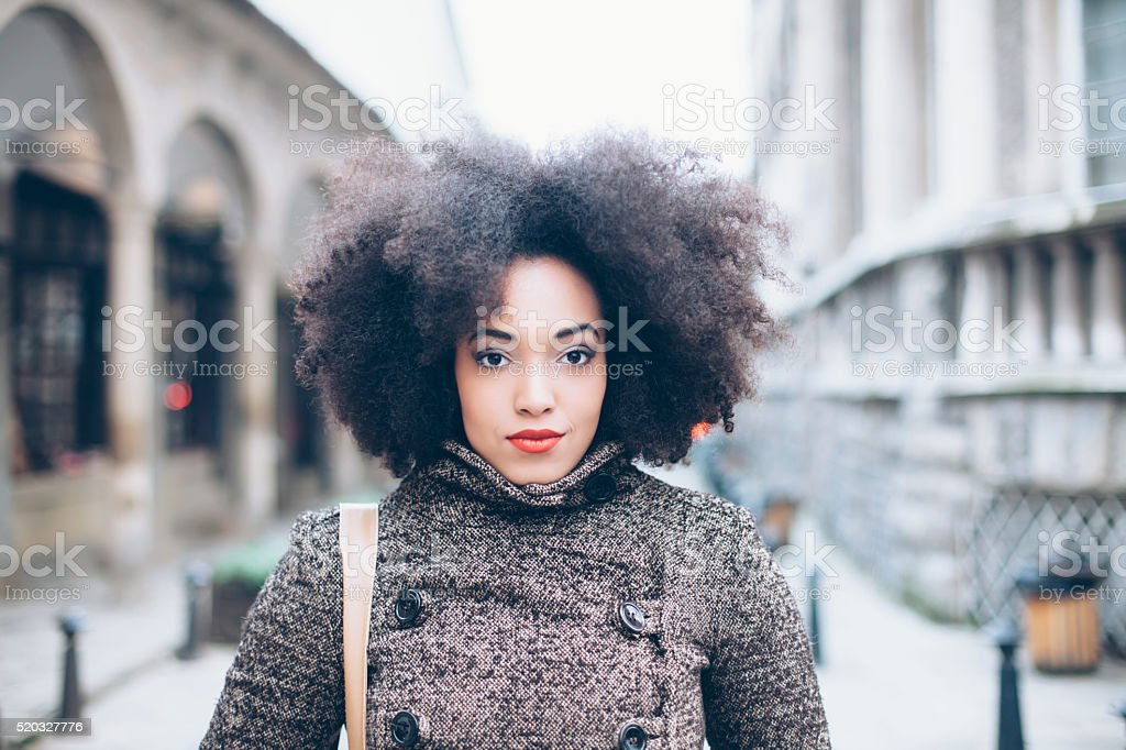 Curly young woman in front of an ancient  building stock photo