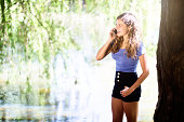 Curly-haired beauty chatting on cellphone under tree by sunny lake