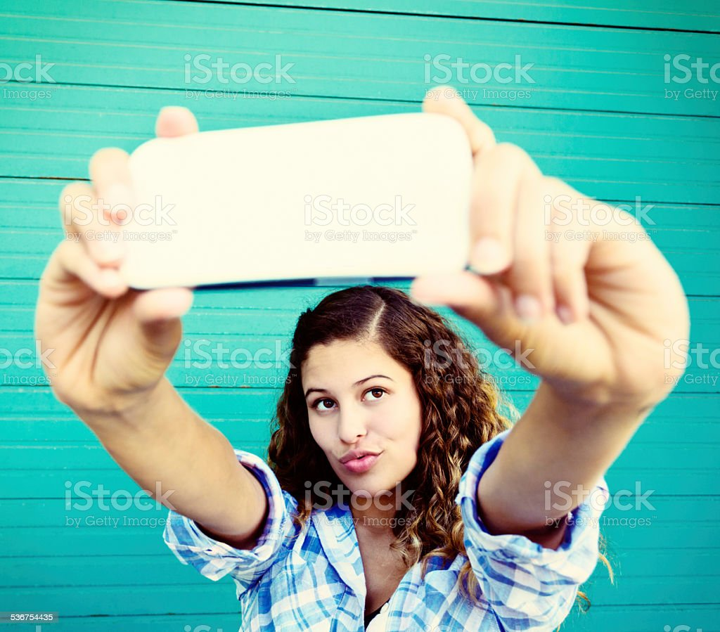 Curly-haired beauty takes trout-pout selfie stock photo
