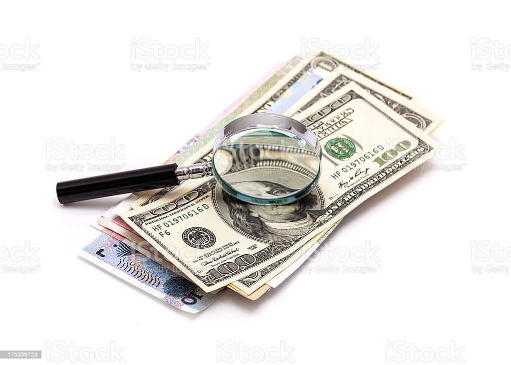 Currencies and magnifying glass royalty-free stock photo