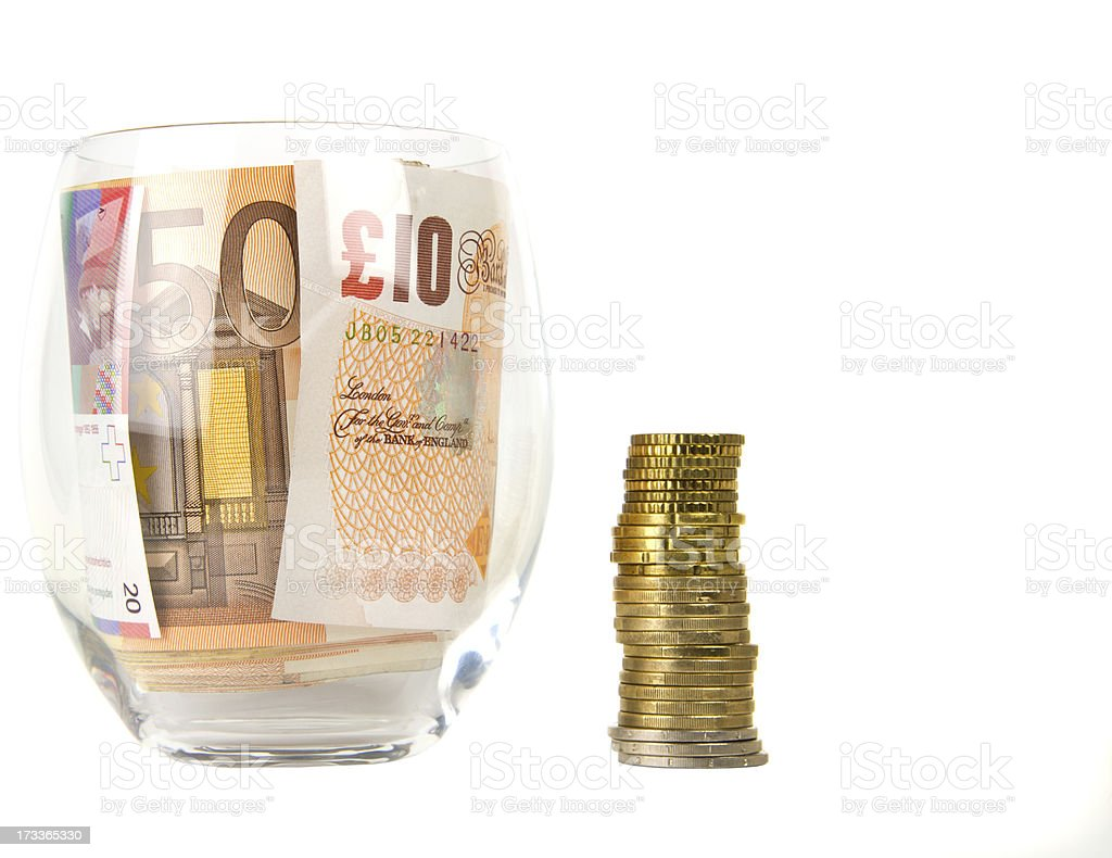 Currency in glass and coins royalty-free stock photo