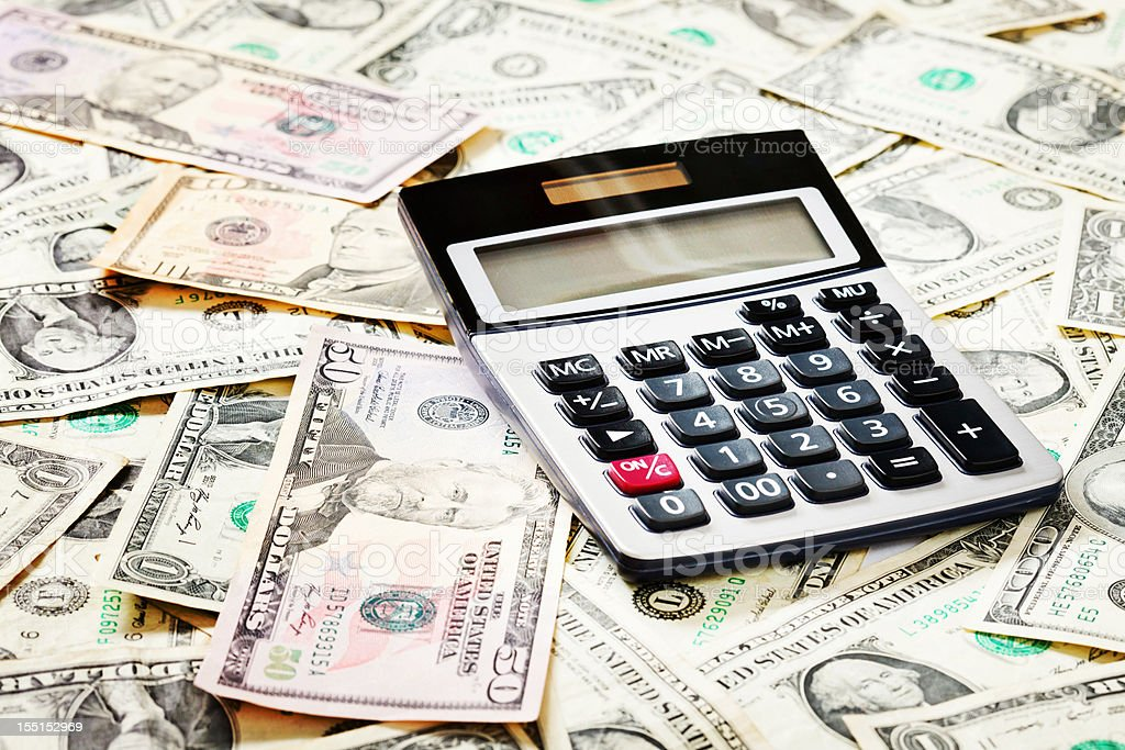 US currency of varying denominations with calculator on top royalty-free stock photo