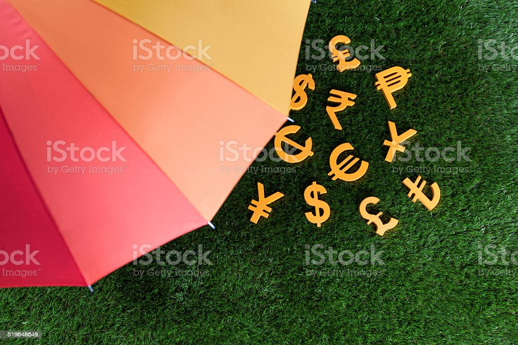 Currency units with colourful umbrella stock photo
