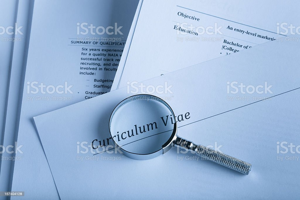 A curriculum vital and a magnifying glass stock photo