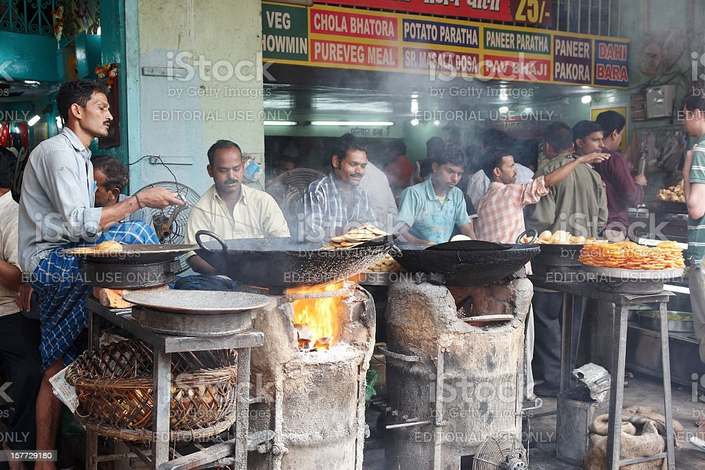 Curry dishes cooking under outdoor fires Indian street scene royalty-free stock photo