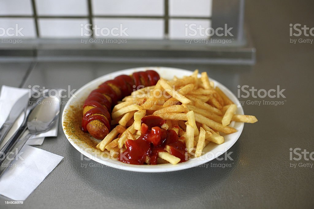 Curry frankfurter with French fries and ketchup royalty-free stock photo
