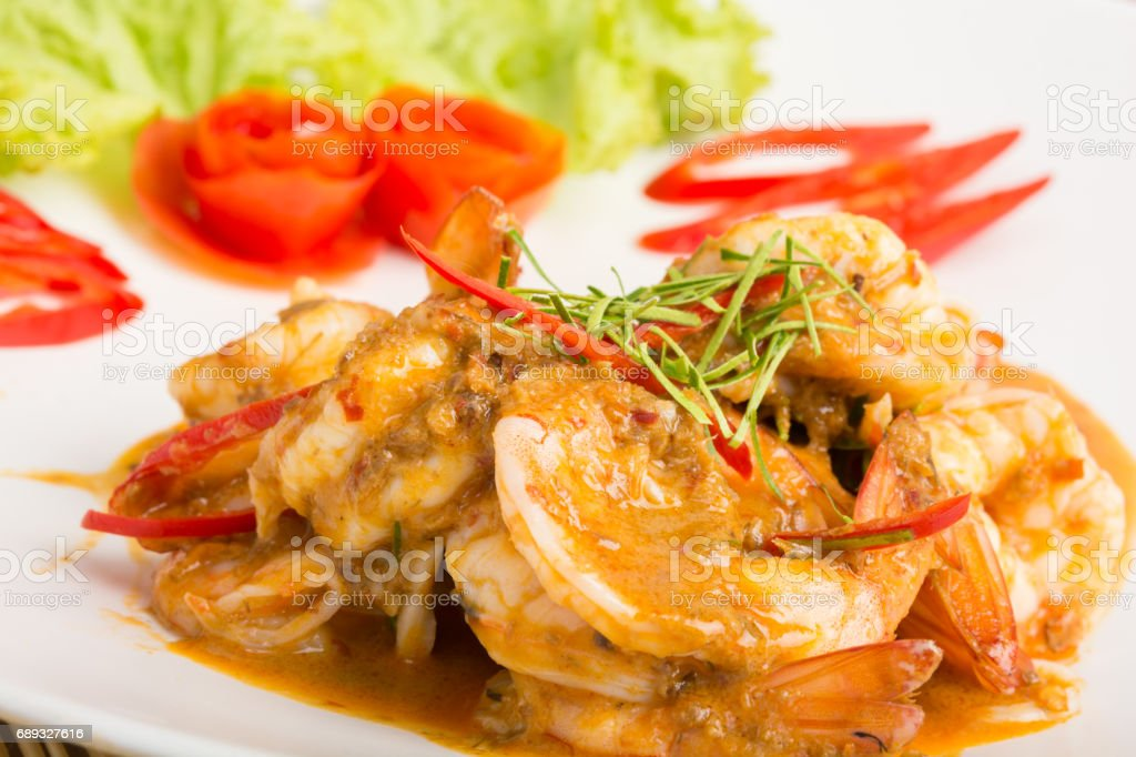 Curry fried shrimps and cooked rice in white dish stock photo