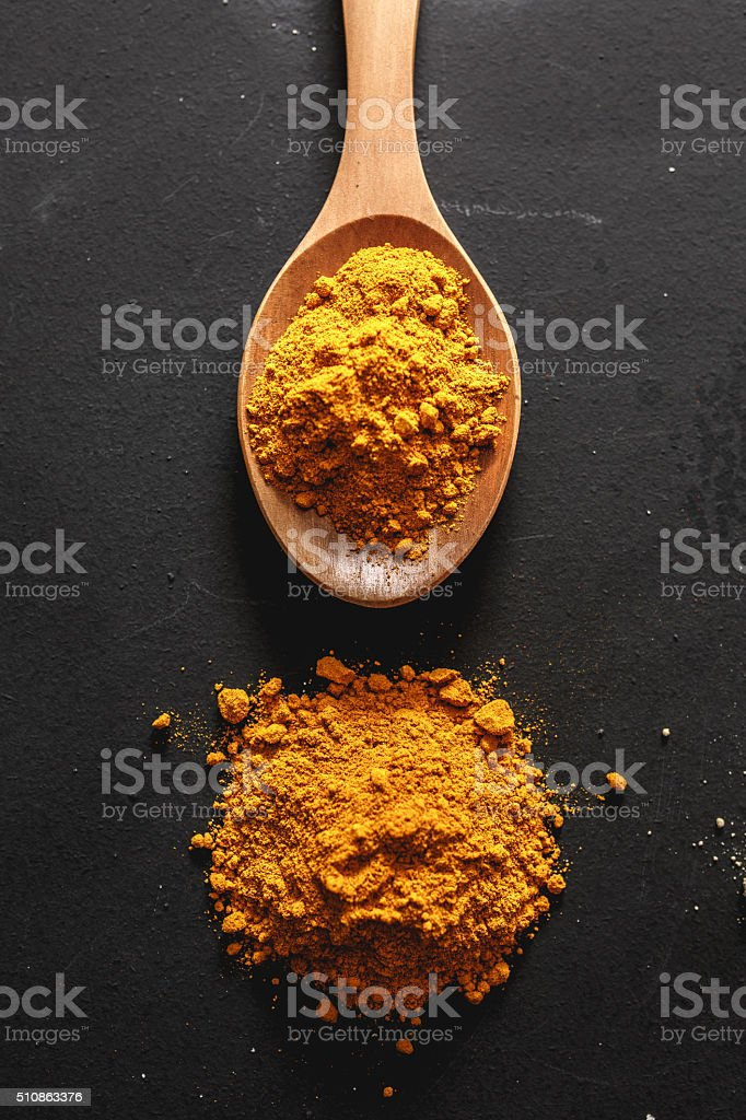 Curry in wooden spoon stock photo