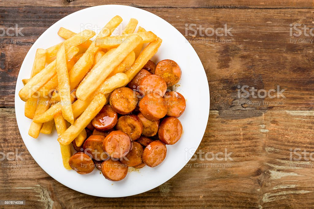 currywurst with fries on a wooden background stock photo