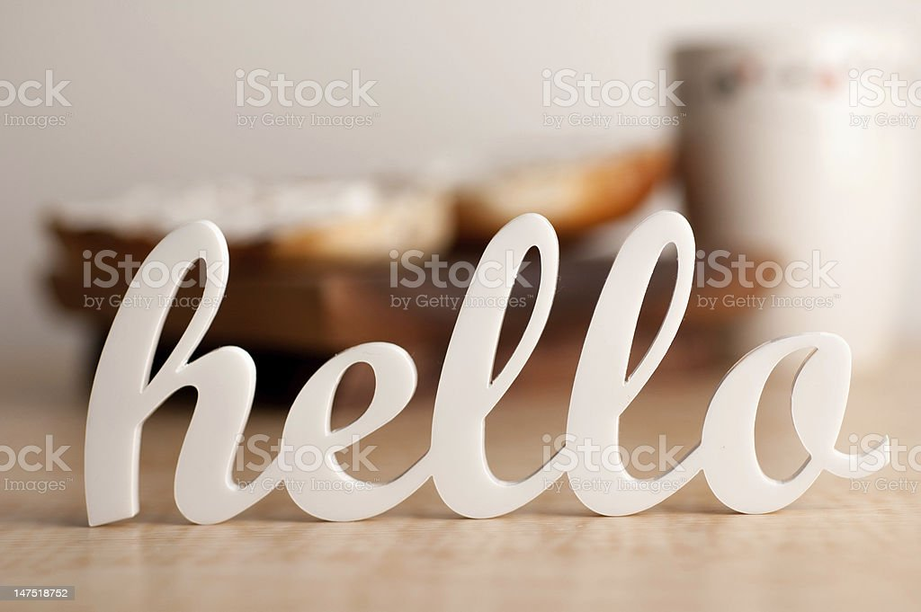 Cursive hello sign with blurred breakfast in background stock photo