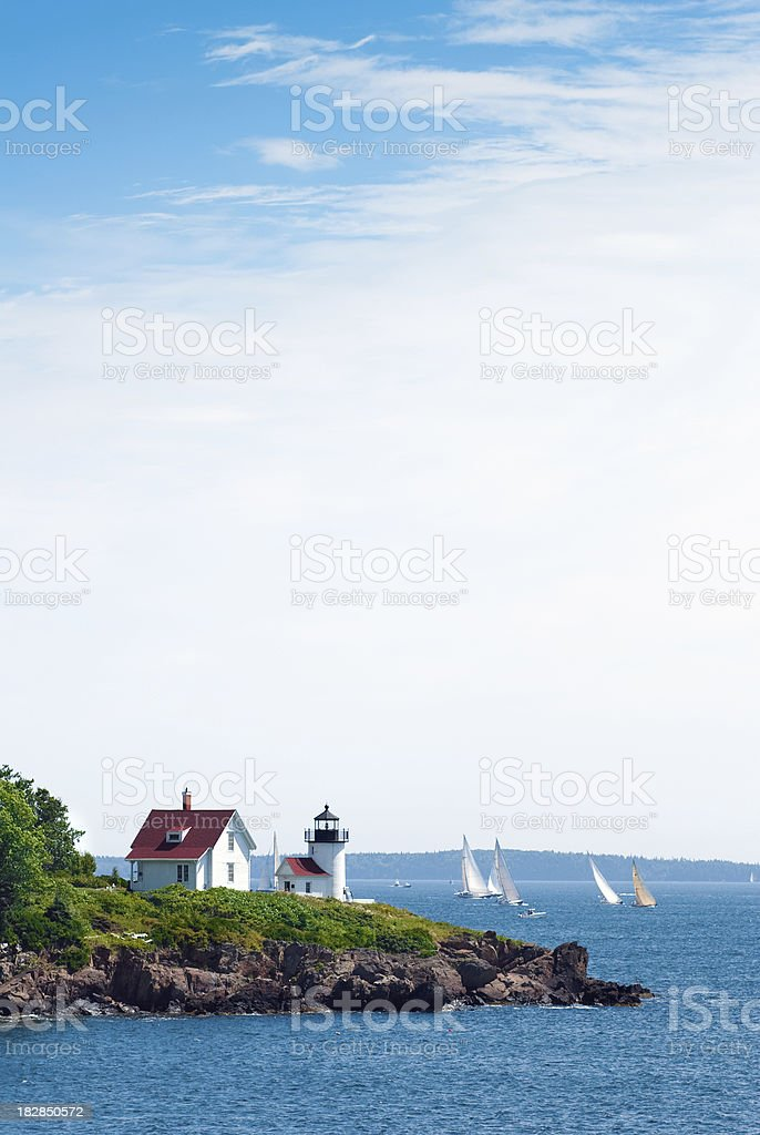 Curtis Head Light in Camden, ME with ocean and sailboats stock photo