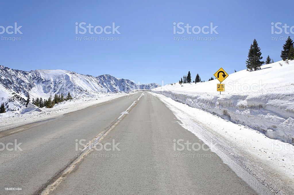 25 MPH Curve Ahead Sign in Mountains Winter stock photo