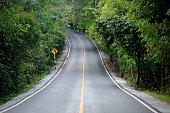 curve concrete road  way to wild