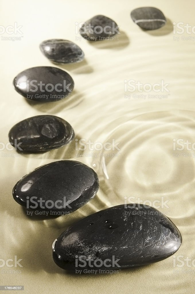 Curve of smooth black pebbles in rippled water royalty-free stock photo