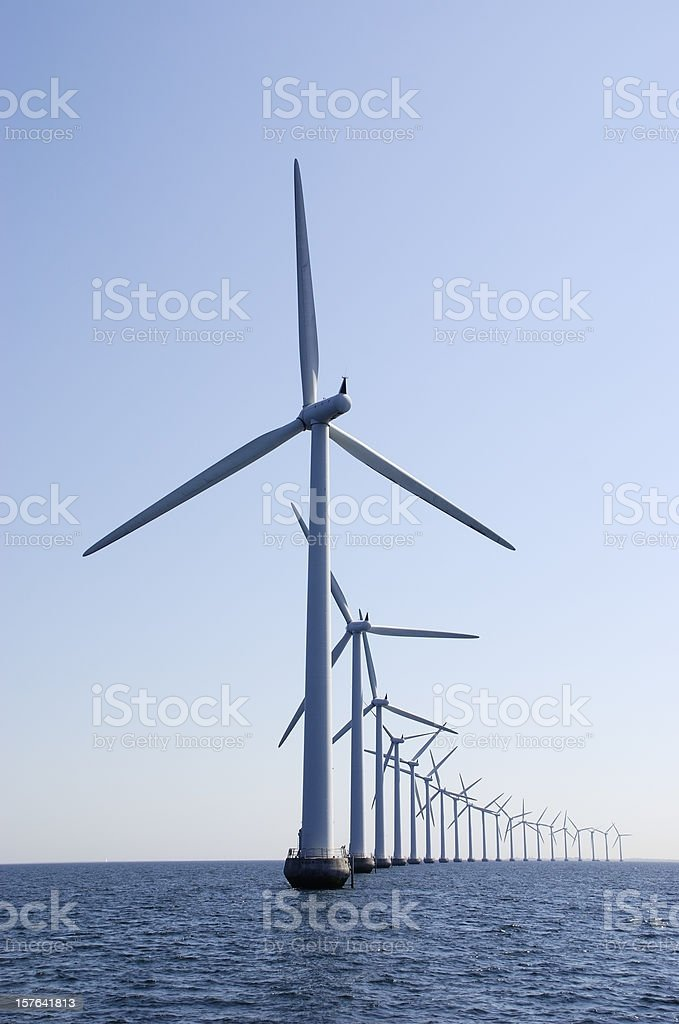 Curve of wind turbines at the ocean, vertical stock photo