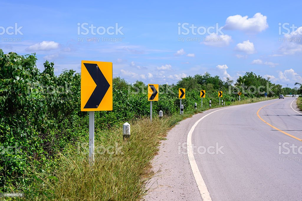 Curve road and right tuning sign with blue sky. stock photo