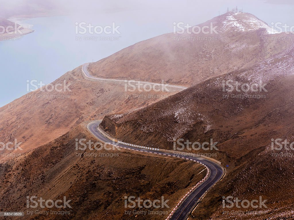 Curved asphalt road in high mountains of Tibet stock photo