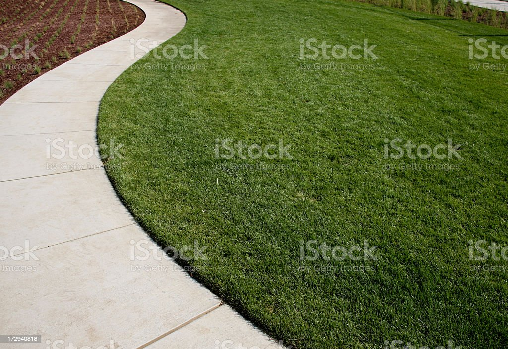 Curved concrete path dividing grass from a garden stock photo