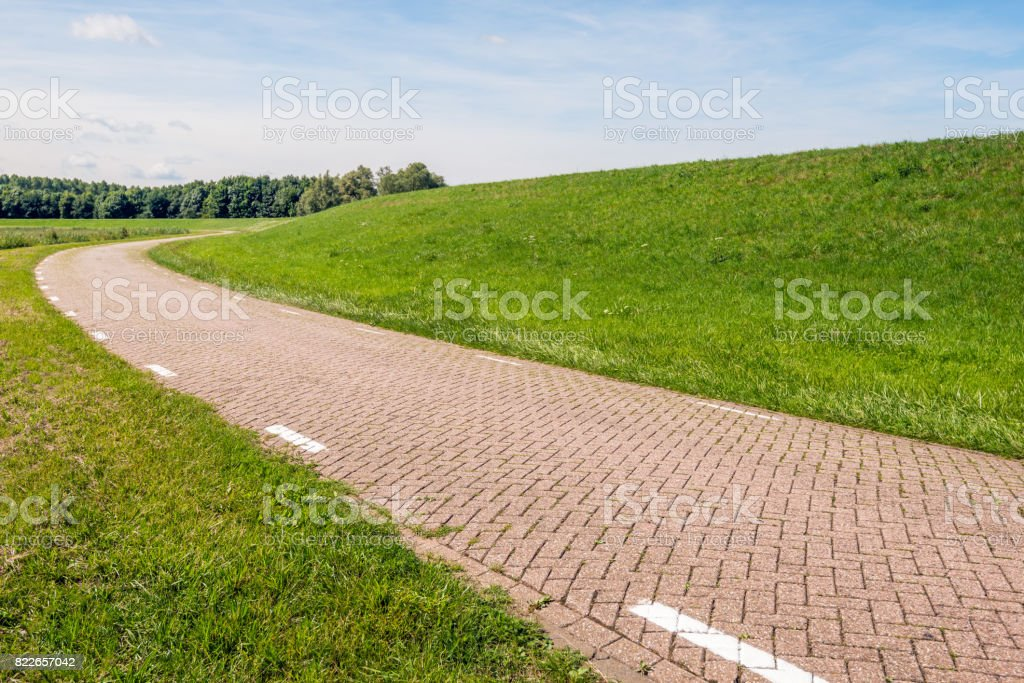 Curved country road beside an embankment stock photo
