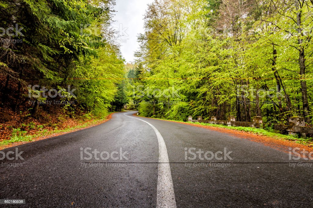 Curved serpentine mountain forest road stock photo