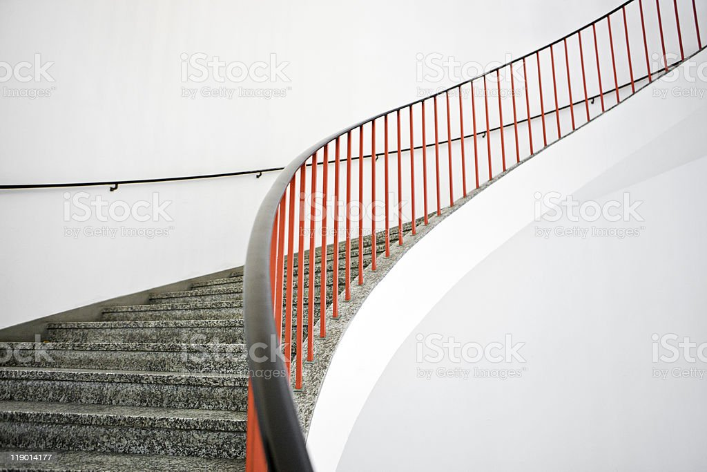 Curved stairs with red banister stock photo