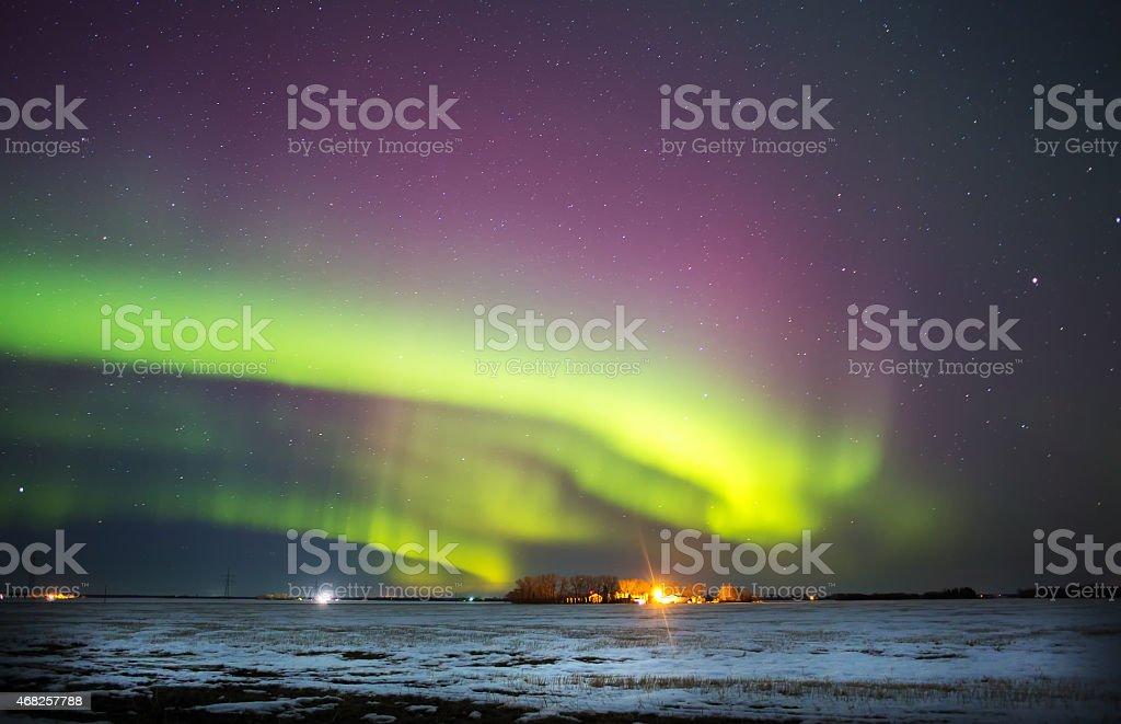 Curving aurora borealis over winter landscape stock photo