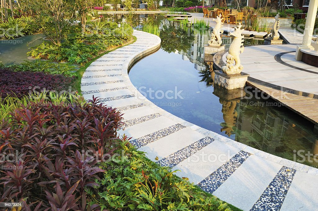 Curving footpath  through a tranquil pond in the garden royalty-free stock photo